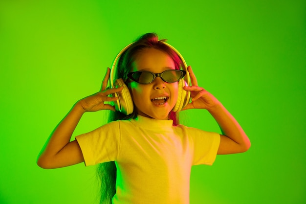 Hermoso retrato femenino de medio cuerpo aislado sobre fondo verde en luz de neón. joven adolescente emocional en gafas de sol. las emociones humanas, el concepto de expresión facial. colores de moda. bailando, sonriendo.