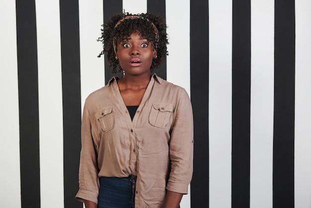 Hermoso retrato femenino en el tipo de fondo de rayas negras y azules. chica afroamericana hace cara sorprendida