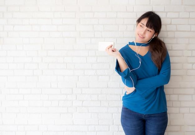 Hermoso retrato joven asiática de pie feliz disfrutar y divertido escuchar música