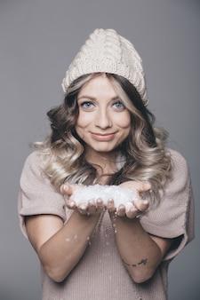 Hermoso retrato de joven mujer atractiva en ropa de punto sobre fondo nevado