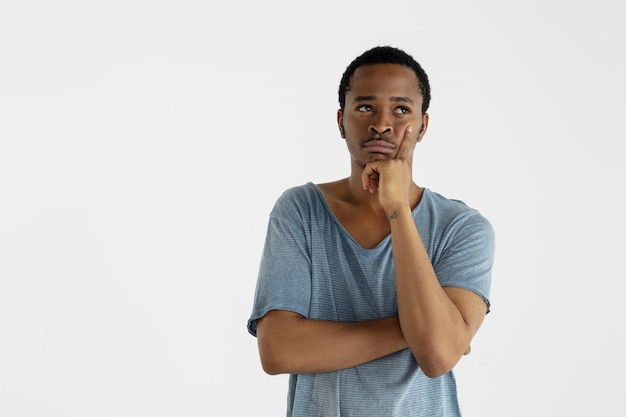 Hermoso retrato masculino de medio cuerpo aislado en la pared blanca. joven afroamericano emocional en camisa azul. expresión facial, emociones humanas, concepto publicitario. pensando, mirando hacia arriba.