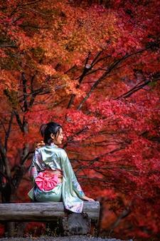 Hermoso retrato de mujer asiática con kimono de oro de japón sentado en un banco de madera en el parque