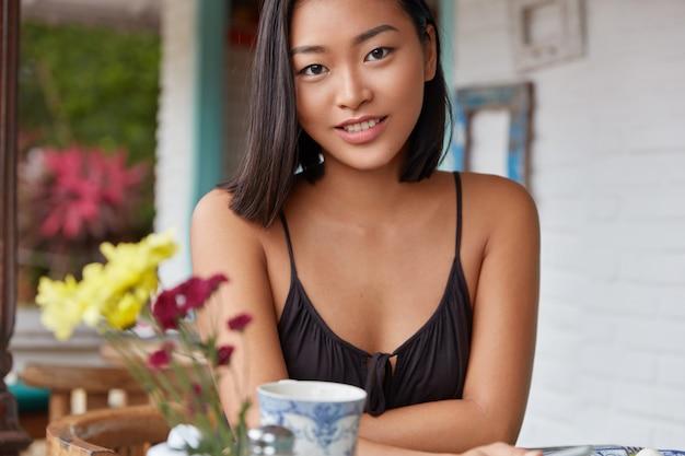 Hermoso retrato de mujer china con peinado bobbed, posa en una acogedora habitación