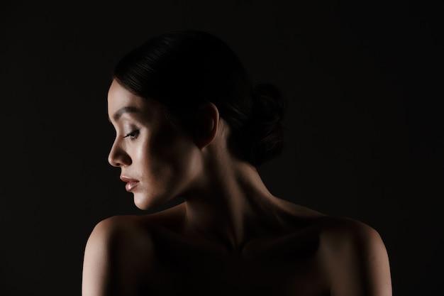 Hermoso retrato de mujer elegante semidesnuda con cabello oscuro en moño poniendo la cabeza a un lado, aislado sobre negro