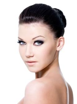 Hermoso retrato de mujer joven y bonita con maquillaje de ojos de moda - aislado