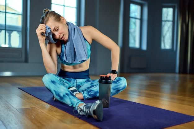 Hermoso retrato de mujer joven relajante ejercicio de forma con una toalla durante un descanso en el gimnasio.