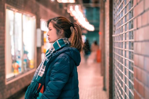 Hermoso retrato de mujer en ropa de invierno por la noche en un callejón en sendai, japón