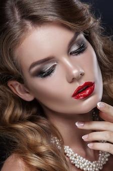 Hermoso retrato de una niña, maquillaje profesional con lápiz labial rojo. en el cuello joyas de perlas, disparadas contra un fondo oscuro. piel limpia, belleza.