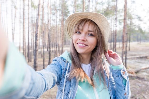 Hermoso retrato de un viajero femenino que toma autorretrato en el bosque