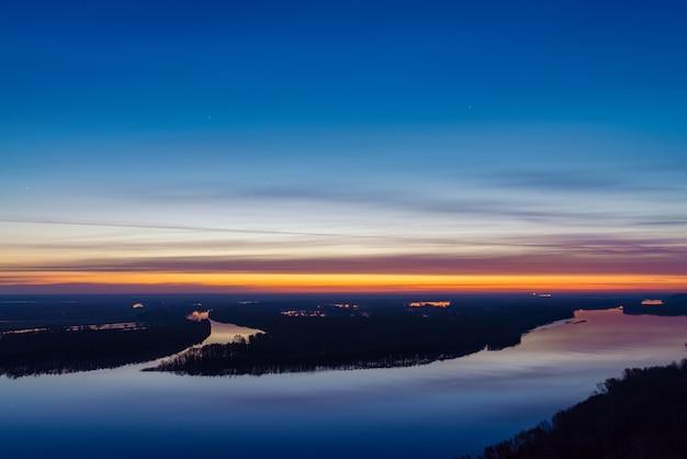 Hermoso río con isla grande con árboles bajo el cielo antes del amanecer.
