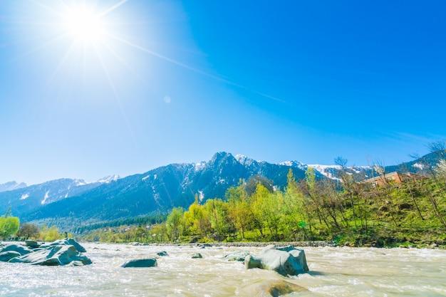 Hermoso río y las montañas cubiertas de nieve paisaje estado de cachemira, india.