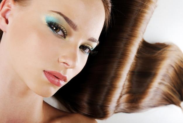 Hermoso rostro femenino con maquillaje ceremonial brillante y cabello exuberante y saludable