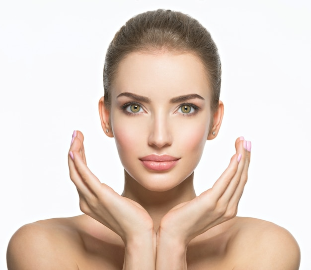 Hermoso rostro de mujer caucásica joven con piel perfecta salud - aislado en blanco. concepto de cuidado de la piel. modelo femenino toca la cara.