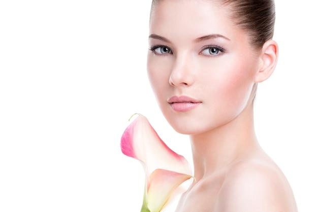 Hermoso rostro de mujer joven y bonita con piel sana y flores rosadas en el cuerpo - aislado en blanco.
