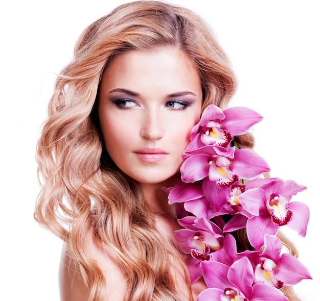 Hermoso rostro de mujer joven rubia con cabellos sanos y flores rosadas cerca de la cara - aislado en blanco.