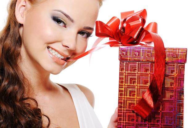 Hermoso rostro de mujer sonriente con una caja roja muerde ligeramente la cinta y dibuja con los dientes