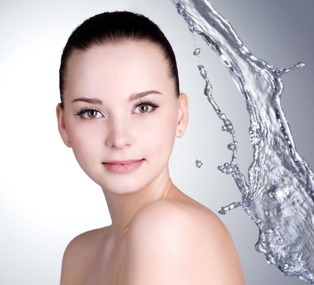 Hermoso rostro con piel limpia y salpicaduras de agua - fondo de color