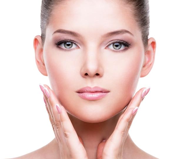 Hermoso rostro sano de la joven mujer bonita con piel fresca tocando la mejilla con las manos - aislado en blanco.