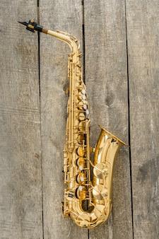 Hermoso saxofón dorado sobre superficie de madera