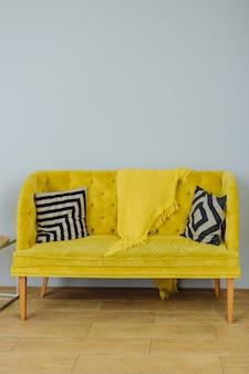 Hermoso sofá amarillo con almohadas en blanco y negro sobre una pared gris