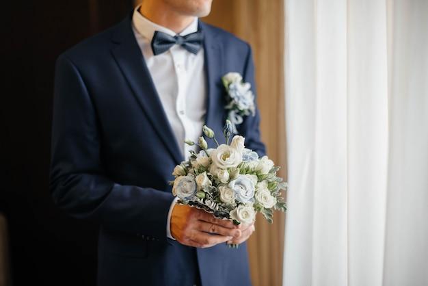 Hermoso y sofisticado primer ramo de boda sostiene a la novia en sus manos junto al novio. ramo de novia y anillos.