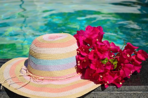 Hermoso sombrero y flores en la piscina. vacaciones en el mar