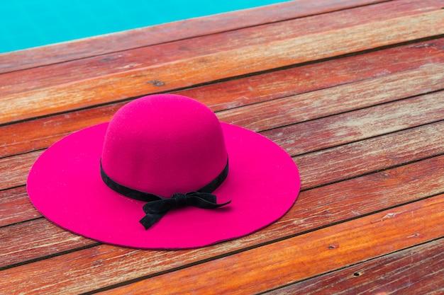Hermoso sombrero rosa con lazo negro en un piso de madera junto a la piscina