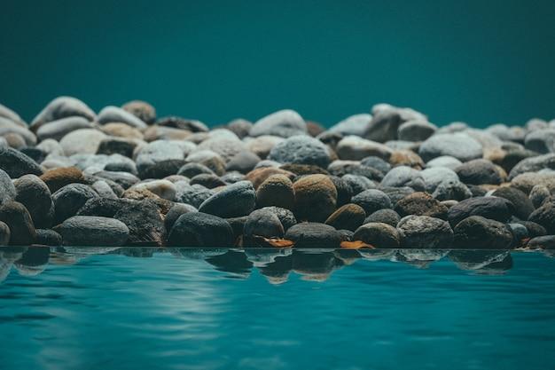 Hermoso tiro de agua en reposo que refleja las rocas