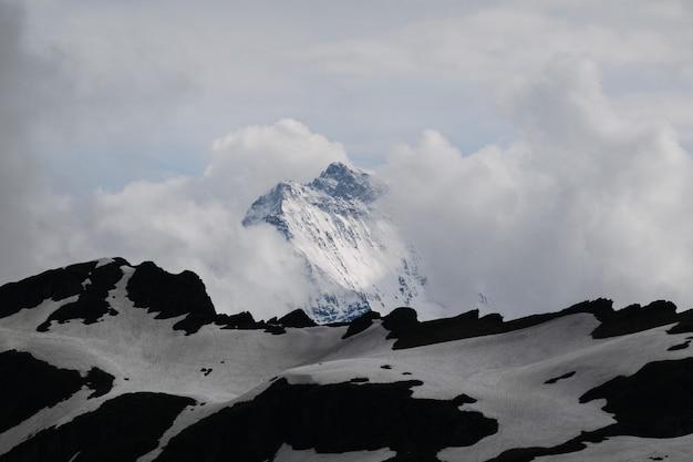 Hermoso tiro de alta montaña blanca bajo el cielo