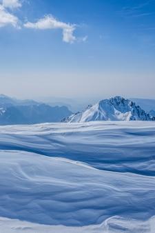 Hermoso tiro de altas colinas blancas y montañas cubiertas de niebla