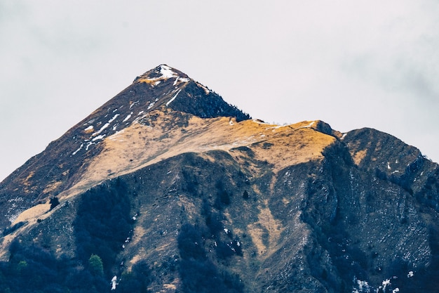 Hermoso tiro de altas montañas rocosas con cielo gris