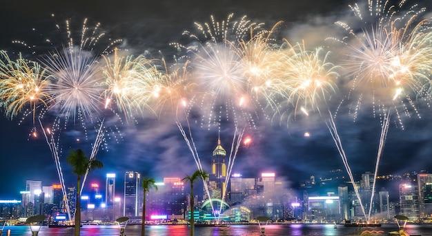 Hermoso tiro ancho de impresionantes fuegos artificiales en el cielo nocturno durante las vacaciones en la ciudad