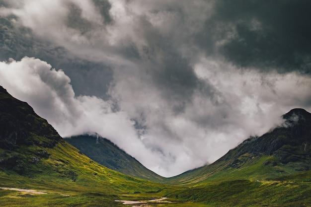 Hermoso tiro ancho de montañas verdes bajo un cielo nublado