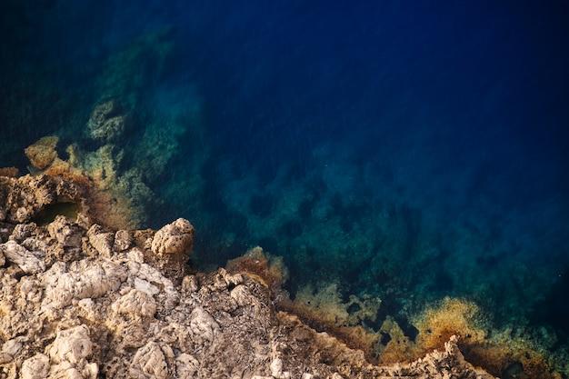Hermoso tiro arriba de los acantilados rocosos del mar en un día soleado