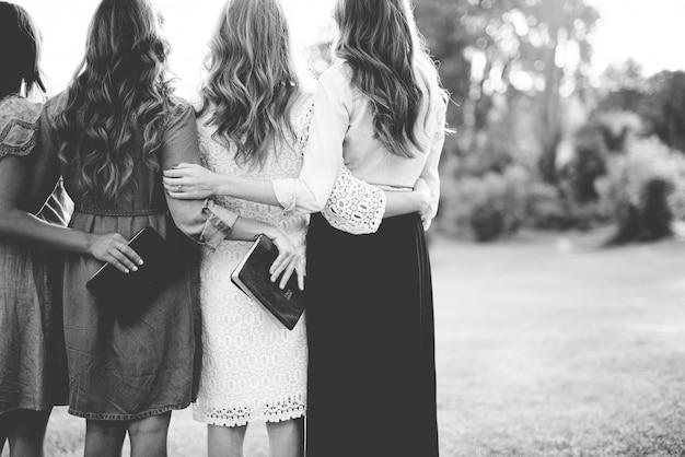 Hermoso tiro desde atrás de las mujeres abrazándose mientras sostienen la biblia