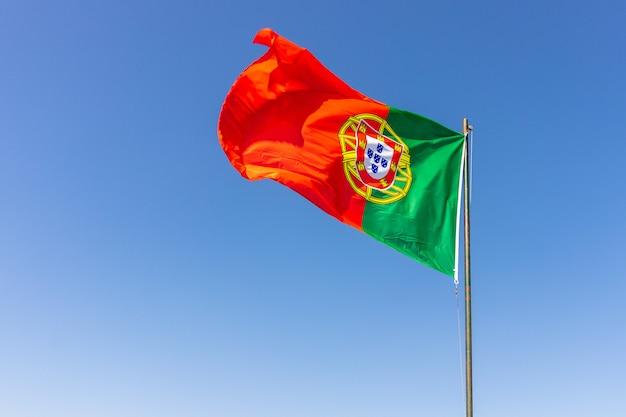 Hermoso tiro de la bandera portuguesa ondeando en el tranquilo cielo brillante