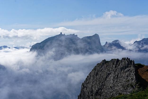 Hermoso tiro desde la cima de la montaña sobre las nubes con una montaña en la distancia