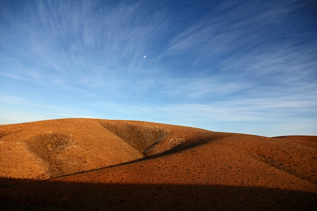Hermoso tiro de colinas desiertas bajo un cielo azul durante el día