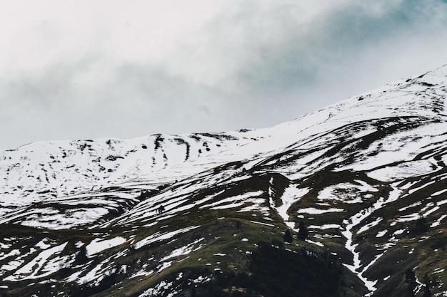 Hermoso tiro de colinas nevadas con cielo nublado