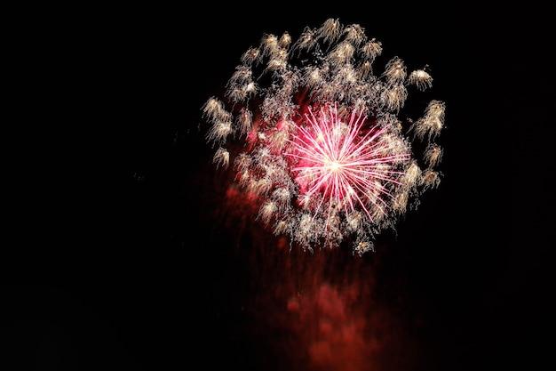 Hermoso tiro de fuegos artificiales estallando en el cielo nocturno que se extiende una atmósfera festiva