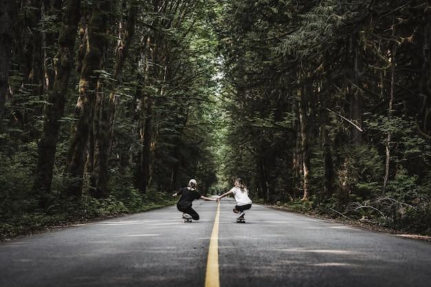 Hermoso tiro de hembras cogidos de la mano blanca patinando sobre una carretera vacía en medio del bosque