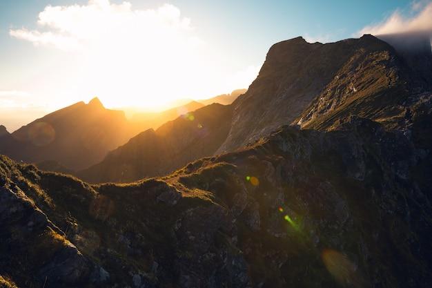 Hermoso tiro horizontal del sol naciente y altas montañas rocosas bajo el cielo nublado