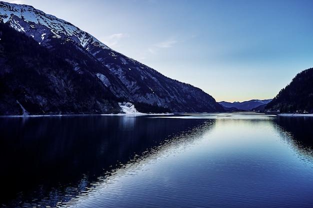 Hermoso tiro de un río con el reflejo de las colinas nevadas y el cielo