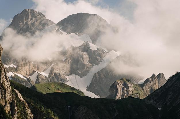 Hermoso tiro de verdes montañas cubiertas de nubes blancas en un cielo azul claro