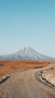 Hermoso tiro vertical de un camino estrecho, curvilíneo y fangoso con una alta montaña