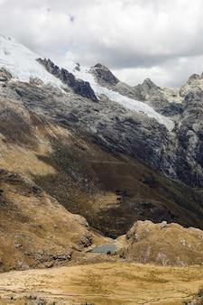 Hermoso tiro vertical de los valles y la nieve en las montañas del huascarán en perú