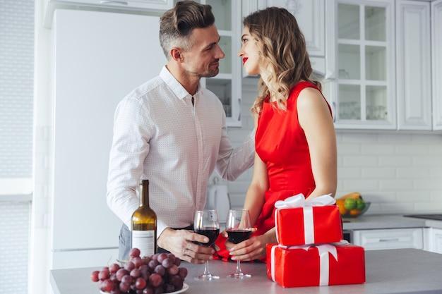 Hermosos amantes celebrando el día de san valentín y bebiendo vino