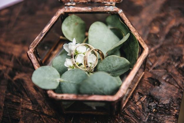 Hermosos anillos de boda con flores frescas en un recipiente de vidrio en el registro de matrimonio en el lugar