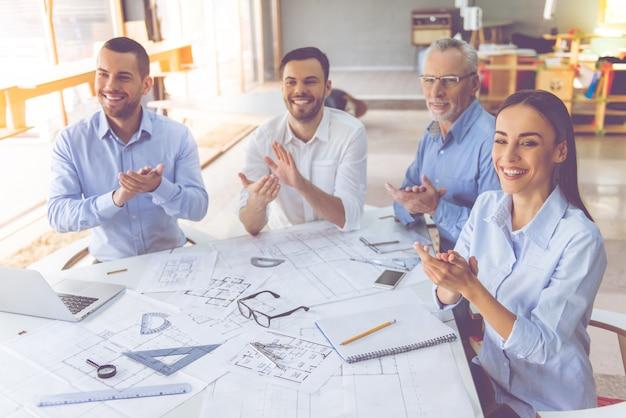 Hermosos arquitectos en camisas clásicas están trabajando en la oficina