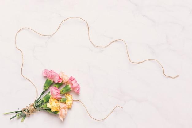 Hermosos claveles y hilo de lino en blanco